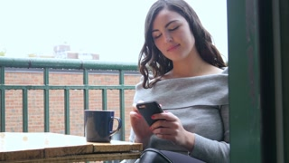 Plus size woman using smart phone on balcony in the morning