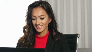 Positive ethnic businesswoman using laptop computer