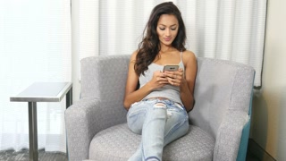 Positive ethnic Indian girl sending text message on smart phone