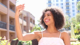 Pretty young ethnic woman taking selfie photo with cell phone