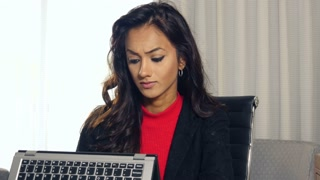 Sad and frustrated ethnic Indian businesswoman working with touchscreen laptop computer