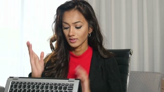 Sad frustrated ethnic Indian businesswoman using touchscreen computer