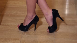 Sexy black high heels with woman's feet