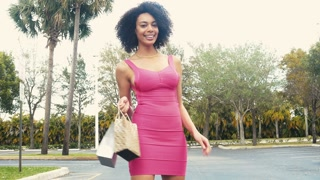 Sexy Ethnic woman walking towards camera with shopping bags