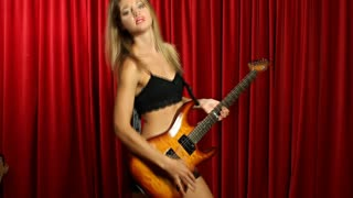 Sexy girl guitar - young woman dancing in front of stage curtains