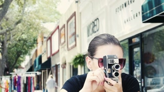Sexy happy hipster girl filming in the city with vintage camera