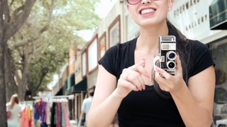 Sexy hipster girl filming with vintage camera in urban scene