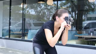Sexy hipster girl filming with vintage camera on the street