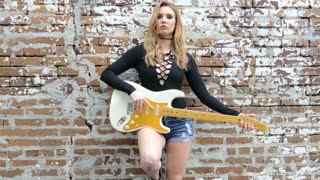 Sexy hipster girl with electric guitar outdoors on grunge wall