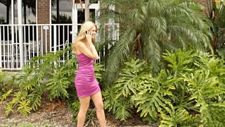 Sexy mature blond businesswoman talking on mobile walking