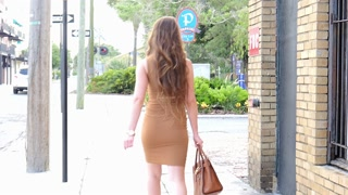 Sexy walk woman on street in tight dress - handheld shot
