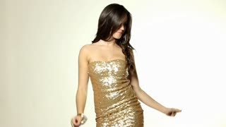 Sexy young woman dancing in tight gold dress with thumbs up