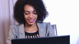 Smiling and laughing ethnic businesswoman working on laptop computer