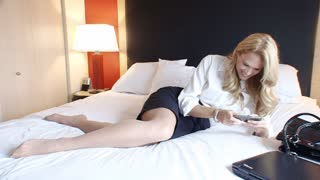 Successful traveling blond business woman on bed sending text message