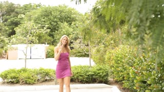sexy mature blond businesswoman talking on mobile walking stock