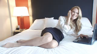 Traveling businesswoman in hotel on mobile phone