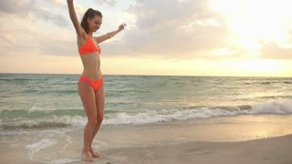 Bikini girl dancing on vacation at the beach at sunset