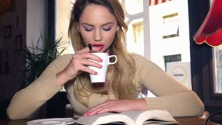 Blonde girl drinking coffee at cafe looking sad and lonely