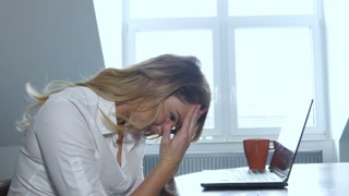 Frustrated and sad young businesswoman working on laptop computer