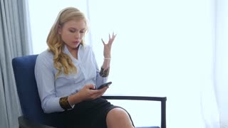 Frustrated young blonde business woman using mobile phone