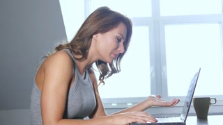Frustrated young ethnic businesswoman working on laptop computer