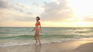Happy bikini girl at the beach at sunset - slow motion