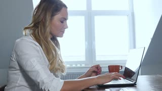 Happy blonde student working on laptop computer at home