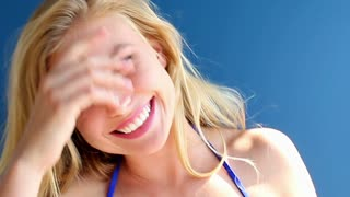Happy blonde teenager girl on holiday at beach smiling big - steadicam shot