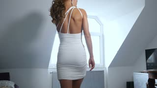 Sexy walk fitness girl in white dress goes to window and looks out