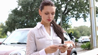 Young attractive businesswoman using smart phone in business parking lot