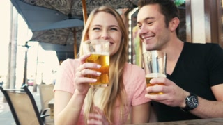 Young couple being silly at cafe with beer on vacation