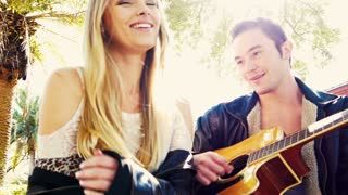 Young couple in love with lens flare and guitar