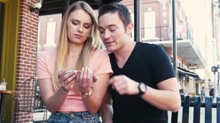 Young couple looking at mobile cell phone on city street