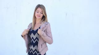 Young hipster girl removing jacket outdoors