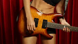 Young woman dancing with electric guitar while playing music