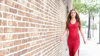 Young woman in red dress walking into focus in urban scene