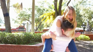 Young woman jumping and riding on back of man - couple in love