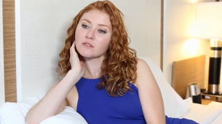 Young woman on bed serious and thinking