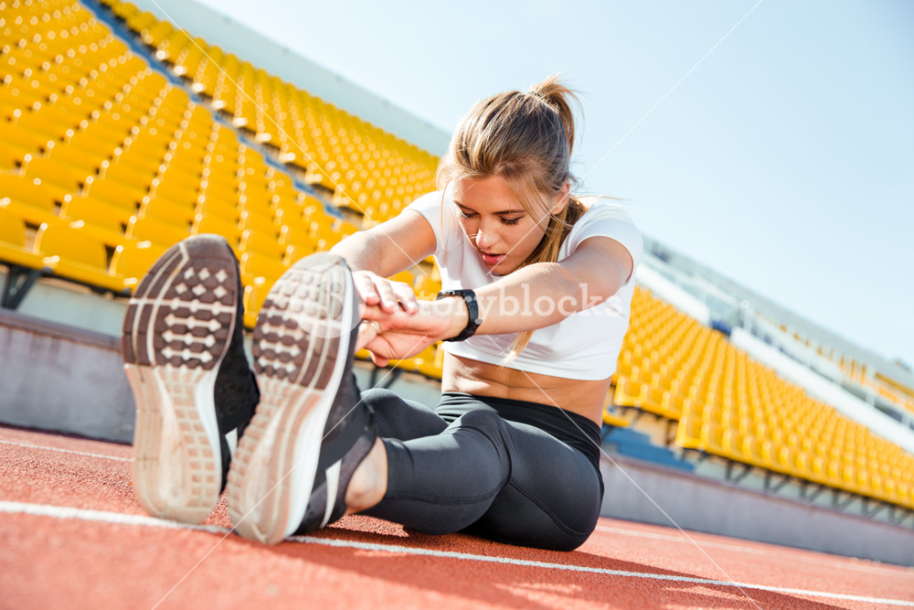 Woman stretching at stadium