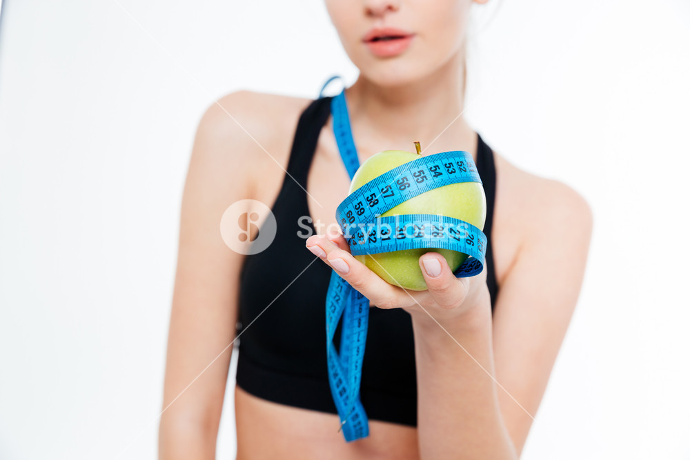 Apple with blue measuring tape held by sportswoman