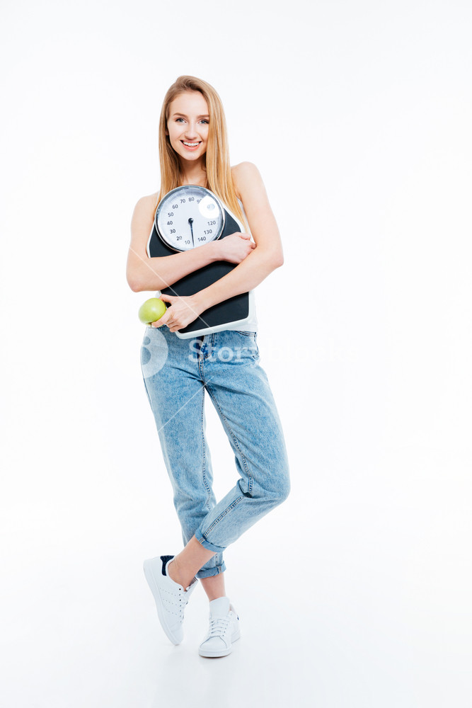 Beautiful joyful woman posing with scales and green apple