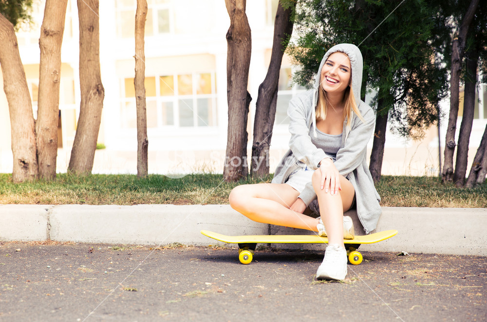 Girl resting with skateboard outdoors