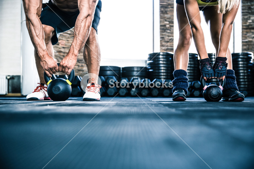 Muscular man and fit woman workout with kettle ball