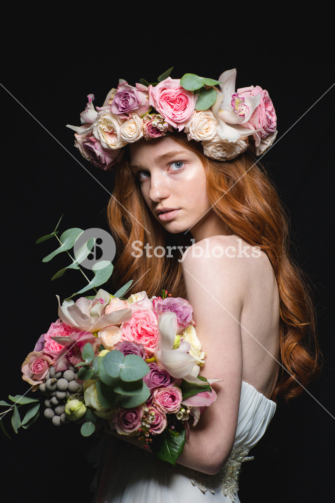 Beautiful redhead woman posing with flowers