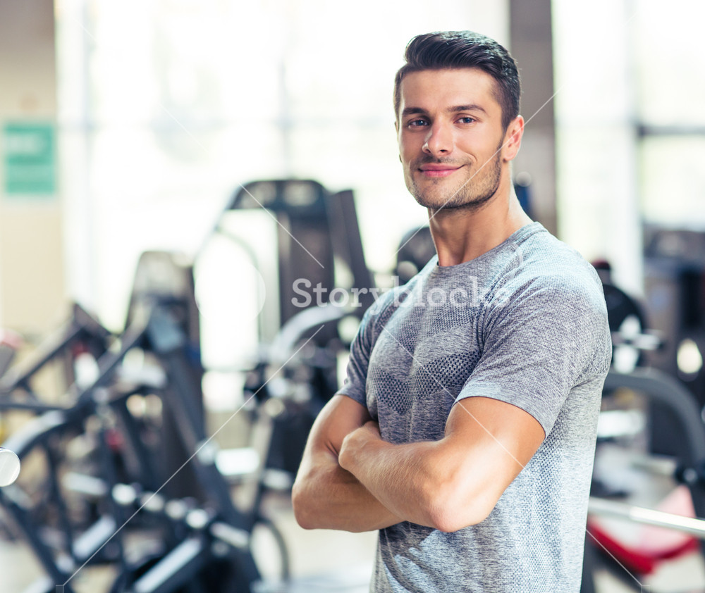 Fitness man standing with arms folded at gy