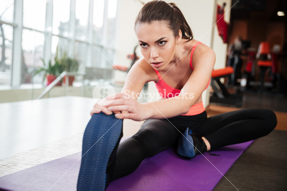 Woman athlete stretching legs on yoga mat in gym