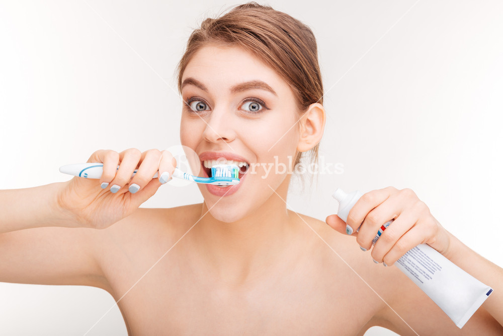 Content lovely woman brushing her teeth with toothpaste and toothbrush