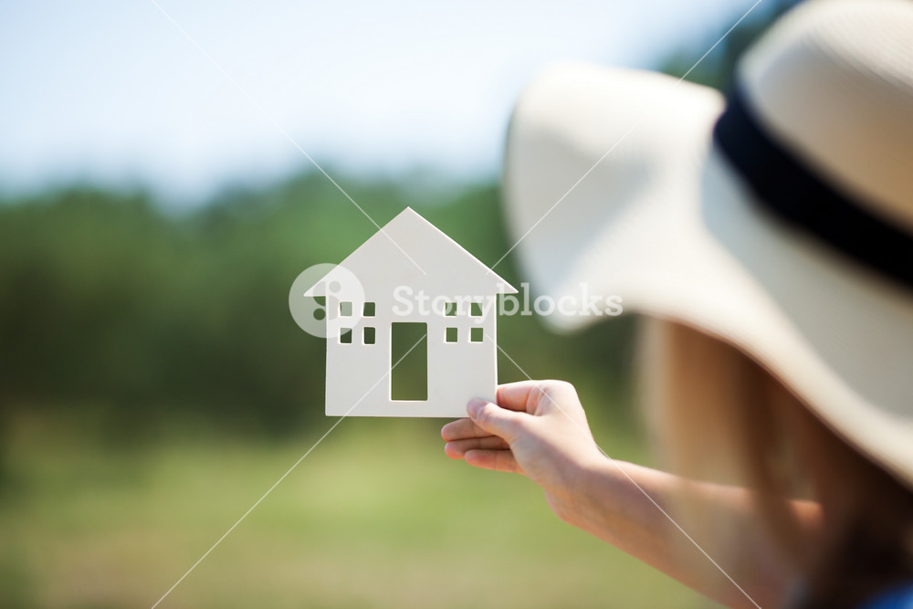 Woman holding house model in the countryside