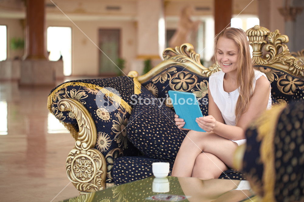 Beautiful woman using tablet in a hotel lobby