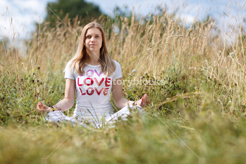 Young girl meditating in the field